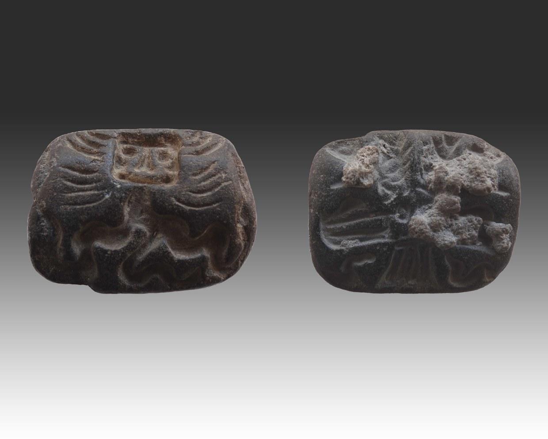 Fotografia di un amuleto-sigillo che raffigura su un lato un personaggio caratteristico della glittica battriano-margiana, dal corpo serpentino e dall'altro un uccello rapace con attributi femminili